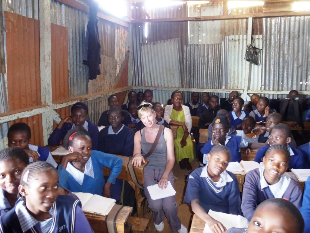 Sarah, a board member and Leah, KCU's Social Worker sitting in class amongst students listening to the teacher.